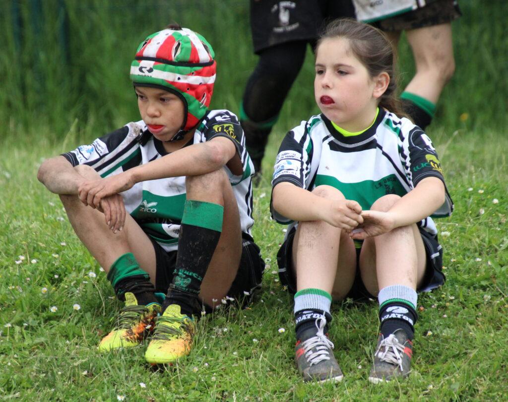 Niño y niña viendo jugar a Rugby